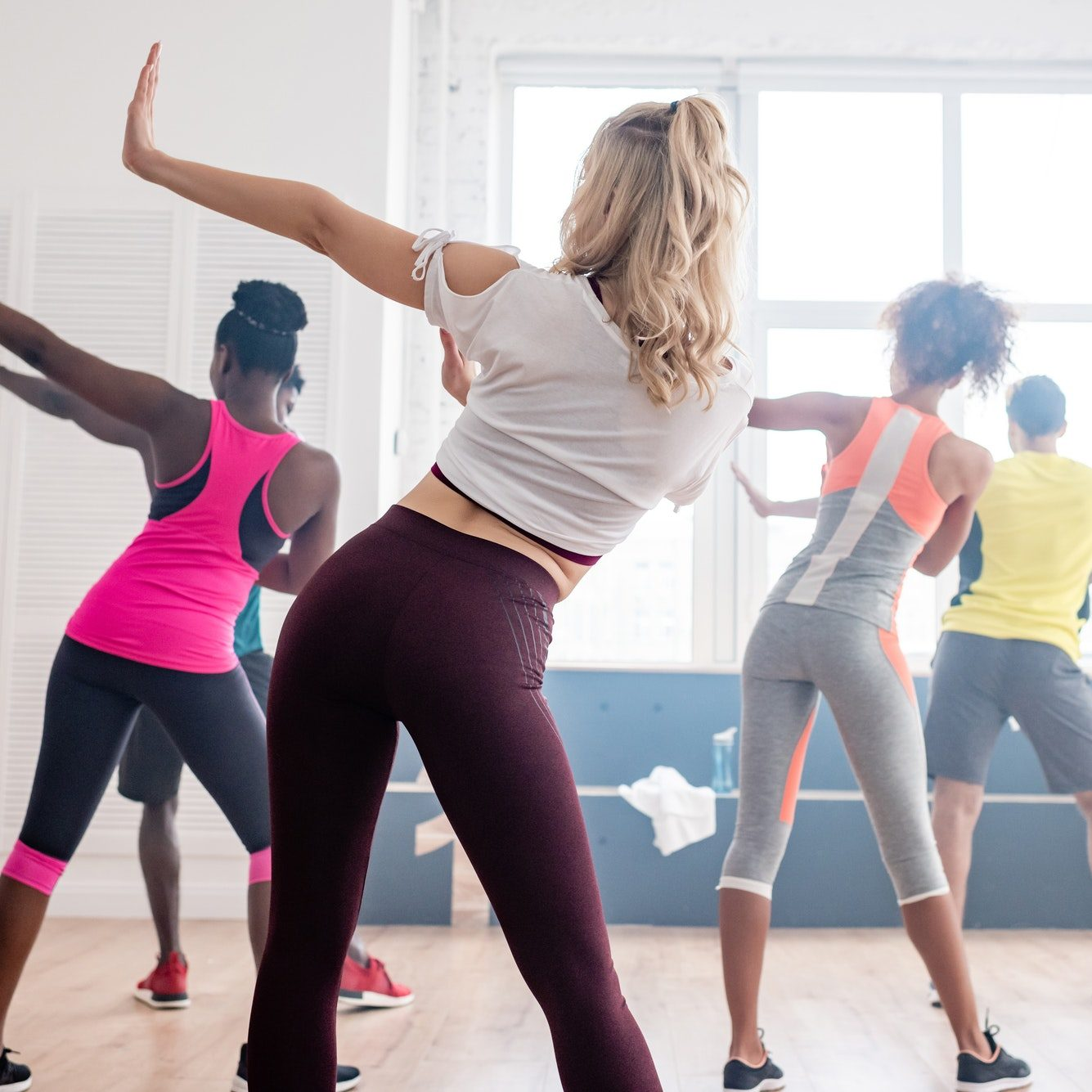 Back view of multiethnic zumba dancers performing movements in dance studio